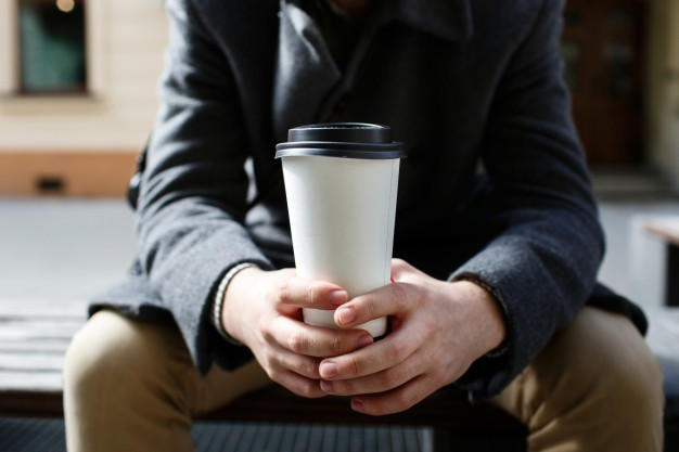 white paper cup of coffee to go in man s arms